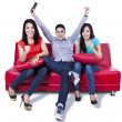 Three young friends cheering at television — Stock Photo