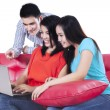 Three young teenagers looking at the laptop — 图库照片