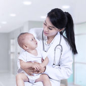 Young female pediatrician holding a baby — Stock Photo