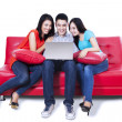 Group of friends sitting in sofa with laptop — Stock Photo #31183929
