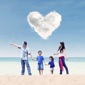Asian family under heart cloud at beach — Stock Photo