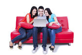 Group of friends sitting in sofa with laptop — Stock Photo