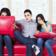 Three young teenagers watching TV — Stockfoto