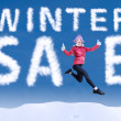 Woman jumping among the word Winter Sale — Stock Photo