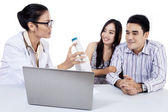 Female doctor discussing with happy couple — Stock Photo