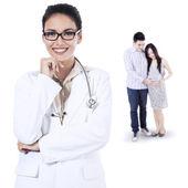 Lachende vrouwelijke arts en zwangere paar — Stockfoto