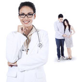 Smiling female doctor and pregnant couple — Stock Photo