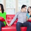 A woman holding hands with man sitting near his girlfriend — Stock Photo