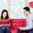 Angry couple on red sofa fighting with pillow — Stock Photo