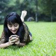 Smiling asian girl using a phone — Stock Photo