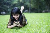 Usmívající se asijská dívka pomocí telefonu — Stock fotografie