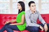 Młoda para siedzi na kanapie po walce — Zdjęcie stockowe