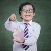 Happy boy puts the coin into a piggy bank — Stock Photo
