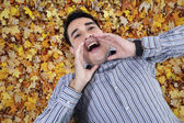Asian young man shouting on leaves — Stock Photo