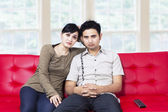 Sad young couple watching television — Stock Photo