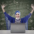 Stock Photo: Happy female muslim with written board and laptop