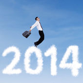 Businessman jumping over clouds of 2014 — Stock Photo