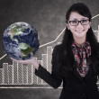 Businesswoman hold globe on growing bar chart chalkboard — Stock fotografie
