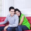 Young couple relaxing on a red sofa at home — Stock Photo