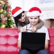 Asian couple in christmas hats shopping online — Stock Photo #33680373