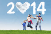Asian family having fun under cloud of new year 2014 — Stock Photo