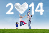 Family celebrate new year 2014 in the nature — Stock Photo