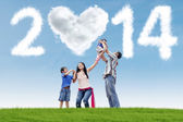 Family celebrate new year 2014 on the meadow — Stock Photo