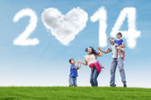 Happy family celebrate new year 2014 outdoor — Zdjęcie stockowe