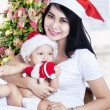 Happy mother and her baby in Santa Claus hat — Stock Photo