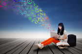 Female student typing on a laptop outdoor — Stock Photo