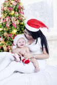 Mother playing with baby near Christmas tree — Stock Photo