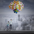 Couple flying with colorful balloons — Stock Photo