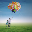 Young couple with colorful balloons — Stock Photo #34257405