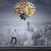 Man flying with balloons — Stock Photo