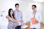 Pregnant couple handshake with obstetrician — Stock Photo
