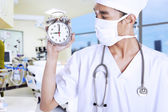A male doctor holding an alarm clock — Stockfoto