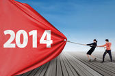 Business team pulling new year 2014 outdoor — Stock Photo