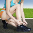 Fitness woman lacing her shoes — Stock Photo