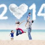 Cheerful family celebrate new year at beach — Stock Photo