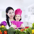 Mother and daughter cooking vegetable salad — Stock Photo