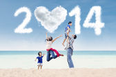 Cheerful family celebrate new year at beach — Stock fotografie