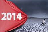Little boy pulling banner of new year 2014 — Stock Photo