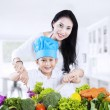 Mother and son cooking vegetable salad — Stockfoto