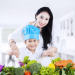 Mother and son cooking vegetable salad — Stock Photo