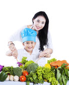 Happy mother and her son preparing a salad — Stock Photo