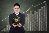 Businessman holding a plant — Stock Photo
