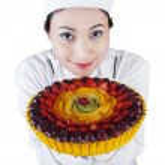 Pretty woman chef holding a dessert cake — Stock Photo