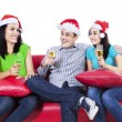 Three teenagers in santa hat drinking wine — Stock Photo