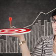 Businesswoman holding up a target — Stock Photo