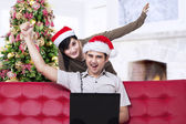 Christmas couple expressing success at home — Stok fotoğraf